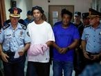 Ronaldinho y su hermano Roberto de Assis Moreira, escoltados por agentes paraguayos, en Asunción.