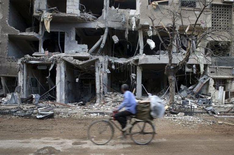 Um homem passa diante de edifícios destruídos em um subúrbio de Damasco.