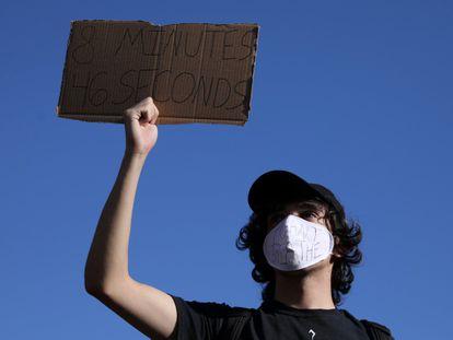 """Um manifestante com uma máscara com os dizeres """"não consigo respirar"""" segura um cartaz que faz menção aos 8 minutos e 46 segundos."""