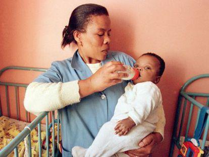 Uma enfermeira do Exército de Salvação em Johanesburgo segura uma criança infectada por HIV, em uma foto de arquivo.