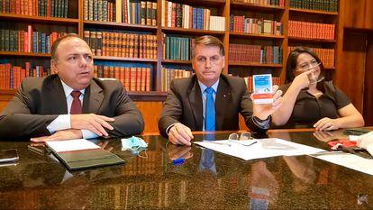"""Ao lado do ex-ministro da Saúde, Eduardo Pazuello, o presidente Bolsonaro segura uma caixa de hidroxicloroquina da empresa Apsen e diz que, no caso dele, o medicamento """"deu certo"""". """"Sou a prova disso"""", afirmo."""