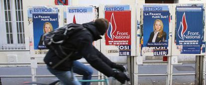 Ciclista passa diante de cartazes de Marion Maréchal em Marselha durante as eleições francesas.