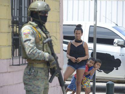 Moradores de Guayaquil observam um dos militares mobilizados desde esta terça-feira nas ruas da cidade.
