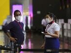 FILE PHOTO: Employees wear masks as a precautionary measure to avoid contracting coronavirus as they work at Guarulhos International Airport in Guarulhos, Sao Paulo state, Brazil, January 31, 2020. REUTERS/Amanda Perobelli/File Photo