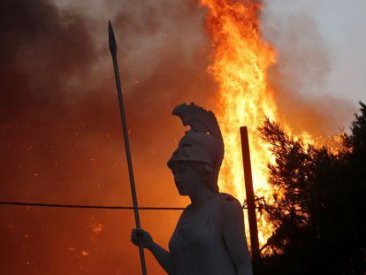 Uma estátua da deusa grega Atena, iluminada por um incêndio ao fundo, em Varympompi, norte de Atenas, na Grécia, em 3 de agosto.