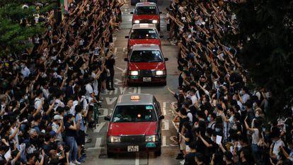 Manifestantes abrem espaço para táxis em Hong Kong durante um protesto em solidariedade ao estudante baleado pela polícia durante os distúrbios de 1º de outubro.