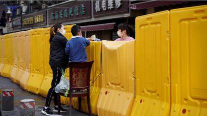 Uma mulher paga a compra de um mercado delimitado por uma barreira levantada durante a quarentena, em Wuhan.
