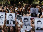 Manifestantes mostram placas com fotos de vítimas da ditadura.