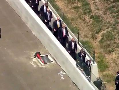 O serviço secreto conduz Trump ao hotel, passando por um terreno.