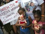 """Children holding dolls covered with fake blood stand next to a sign that reads in Portuguese """"Stop killing our children. We love you"""" during a protest against the killing of Emily Victoria Silva dos Santos, 4, and Rebeca Beatriz Rodrigues dos Santos, 7, in Duque de Caxias, Rio de Janeiro state, Brazil, Sunday, Dec. 6, 2020. The girls were killed by stray bullets while playing outside their homes. (AP Photo/Bruna Prado)"""