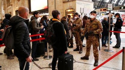 Agentes da polícia e soldados revistam passageiros em um posto de controle na estação central de Milão.