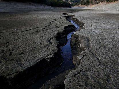 Um fluxo de água atravessa o fundo seco de um reservatório em San Jose, na Califórnia.