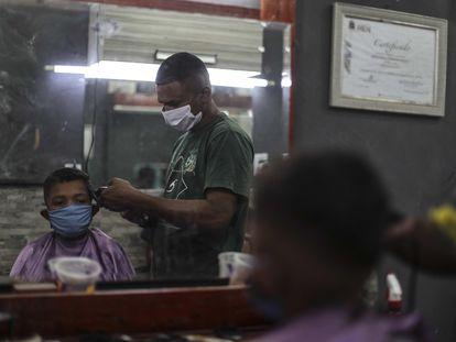 Um barbeiro da favela de Mandela, no Rio de Janeiro, trabalha com máscara de proteção durante pandemia de coronavírus.