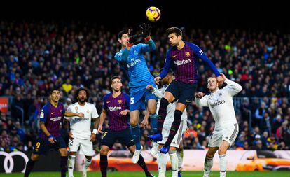 Courtois e Piqué disputam bola alta no primeiro clássico da temporada, no Camp Nou, quando o Barça venceu por 5 a 1.