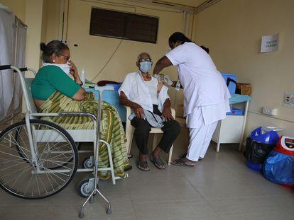 Uma enfermeira injeta uma vacina contra a covid em um idoso no Raman Hospital de Bangalore (Índia).