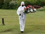 A funeral service worker wearing a mask and protective coveralls carries flowers during the funeral of Munuse Nabi, who died from the coronavirus disease (COVID-19), at a cemetery in London, Britain, April 28, 2020. Picture taken April 28, 2020.    To match Special Report HEALTH-CORONAVIRUS/BRITAIN-ELDERLY    REUTERS/Peter Nicholls