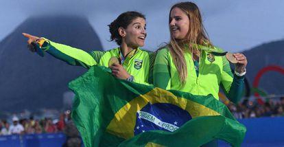 Martine e Kahena seguram a bandeira do Brasil no pódio.