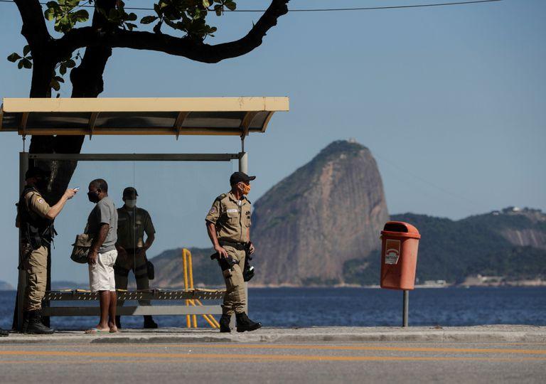 Um oficial de segurança mede a temperatura de um homem nesta segunda-feira em Niterói, uma das primeiras cidades do Rio de Janeiro a endurecer as medidas restritivas.