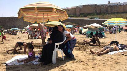 A feminista marroquina Betty Lachgar, na sexta-feira, 27, na praia Oudayas, em Rabat, ao lado de Hanan (sentada), que veste um 'niqab'