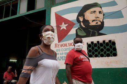 Pedestres caminham diante de uma imagem de Fidel Castro, neste domingo, em Havana.