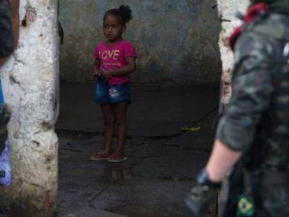 Garota observa rapaz é interrogado por soldados do Exército na Vila Kennedy, no Rio.