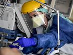 Nursing staff dressed personal protective equipment (PPE) look after a patient in the Intensive Care unit at the Sint-Trudo hospital in Sint-Truiden on April 17, 2020, as measures announced on March 18, 2020, in Belgium to avoid the spread of the novel coronaviru, Covid-19, will remain active until May 4. (Photo by DIRK WAEM / various sources / AFP) / Belgium OUT