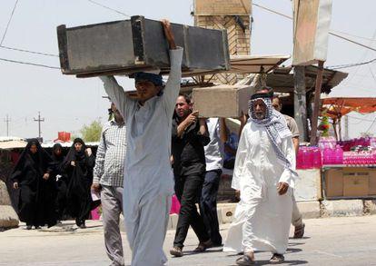 Familiares de soldados iraquianos transportam seus restos mortais.
