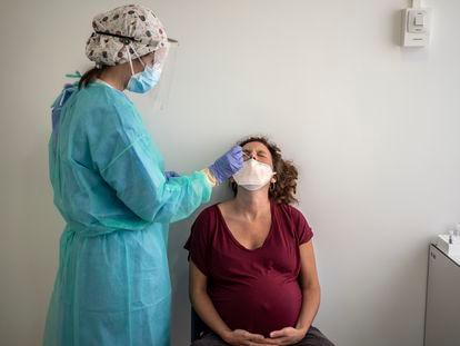 Funcionária de hospital de Madri colhe amostra de uma grávida para fazer um exame de coronavírus, em maio.