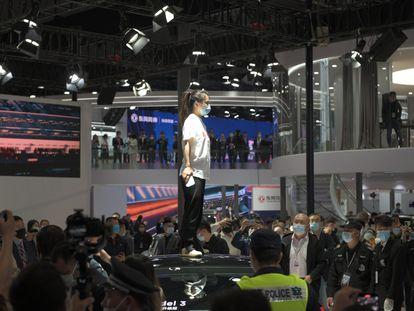 Uma mulher protesta contra a Tesla subindo num veículo da marca no Salão do Automóvel de Xangai.