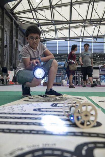 Menino se diverte com o robô guiado por luz que montou no TokyLabs.