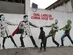 "A woman passes by a graffiti with Brazilian President Jair Bolsonaro and a person depicting the coronavirus pulling a rope against health workers in Sao Paulo, Brazil, June 10, 2020. The graffiti reads:""Which side are you?"". REUTERS/Amanda Perobelli"