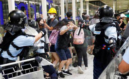 Polícia usa gás de pimenta contra os manifestantes do aeroporto de Hong Kong.