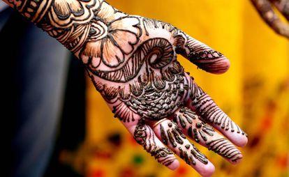 Estudante posa enquanto lhe fazem uma tatuagem de hena em Bhopal, na  Índia.