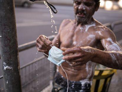 Morador de rua lava máscara em torneira improvisada em São Paulo, na última terça-feira. ANDRÉ LUCAS /