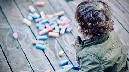 Uma criança desenha com giz no chão.