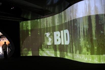 Um homem em frente a um logo do BID, em um centro de convenções no Panamá.