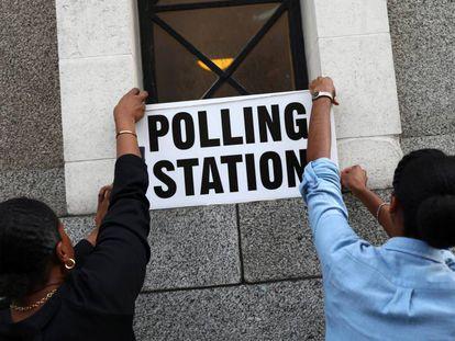 Trabalhadores colocam cartazes em um colégio eleitoral de Londres.
