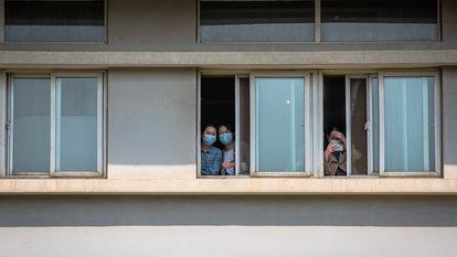 Um grupo de mulheres com máscaras olha do Hospital Jinjiantang, em Wuhan.