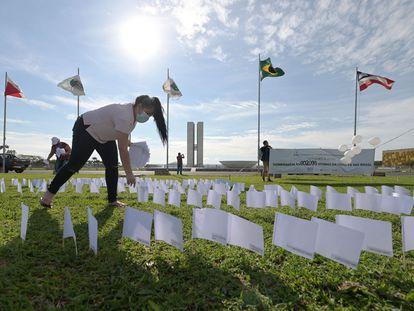 Membros da Associação de Vítimas e Famílias de Vítimas da Covid-19 (AVICO) colocam 600 bandeiras brancas em frente ao Congresso Nacional, em Brasília, em homenagem aos 600.000 mortos durante a pandemia no Brasil.