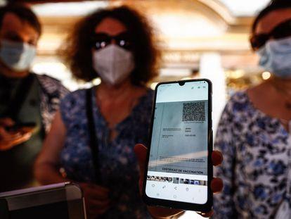 Mulher mostra seu certificado de vacinação em um restaurante no Monte Saint-Michel, na Normandia, França.
