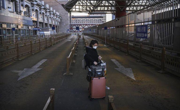 Mulher em um estacionamento de táxi vazio uma estação de trem na região oeste de Pequim.