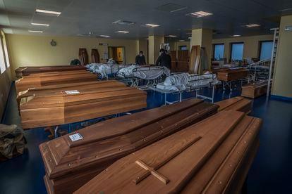 Funcionários de uma funerária preparam caixões em Bérgamo.