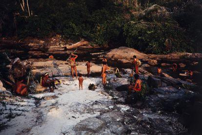 Um grupo de indígenas araweté na margem de um rio após um dia de caça.