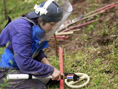 Uma mulher procura minas com um detector de metais