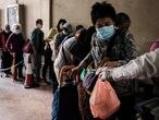 People wearing facemasks as a precautionary measure against the COVID-19 coronavirus, queue up for free meal boxes given out by Gingko House restaurant workers (R) and volunteers from the basement of their Yau Ma Tei branch in Hong Kong on March 27, 2020. - Gingko House is a social enterprise devoted to promoting elderly employment in catering services. It has been giving away free meal boxes for lunch and supper at one of its branches in Yau Ma Tei for more than two years. In the past half year, registered meal box recipients doubled to nearly 1,000, according to project manager and social worker Joyce Mak. (Photo by Anthony WALLACE / AFP)