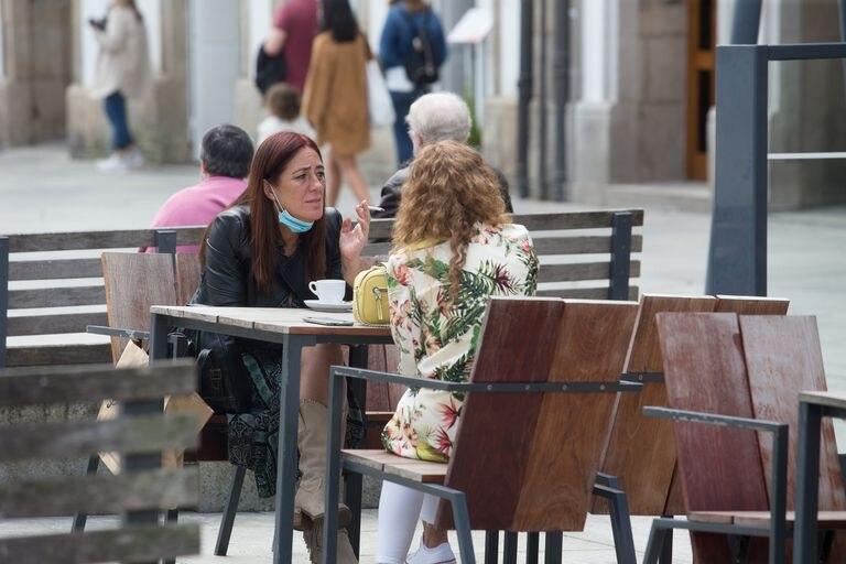 Pessoas fumando em um café na Galícia nesta quinta-feira. Nesta sexta, o Governo espanhol anunciou a proibição de que fumar na rua, caso não seja possível manter uma distância de dois metros das demais pessoas.