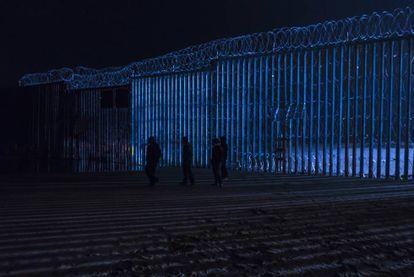Um grupo de pessoas caminha diante do muro fronteiriço de Tijuana, na sexta-feira à noite.