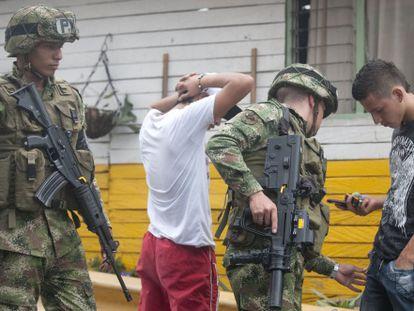 Militares revistam jovens na periferia de Medelín.