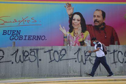 Homem passa em frente a um cartaz com a imagem de Daniel Ortega e Rosario Murillo, na capital Manágua.