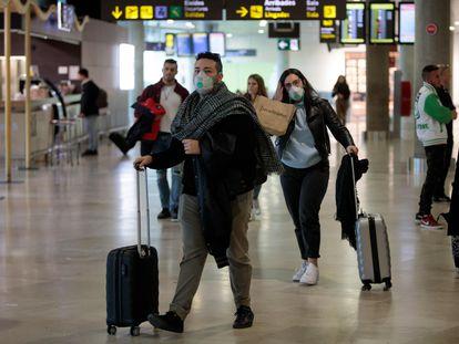 Passageiros procedentes da Itália chegam com máscaras no aeroporto de Manises, em Valência, na Espanha.